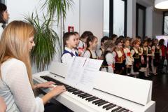 Učiteljica za klavirom svira horske pesme za decu